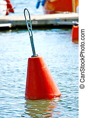 A red buoy floating on boat parking