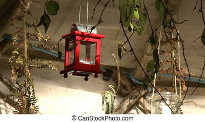 A red candle holder lantern hanging from the ceiling in a white tent