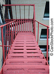 A red fire escape in an urban setting.