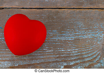 A red heart on the wooden background