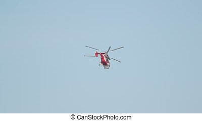 A red helicopter flies into the horizon in a clear sky....