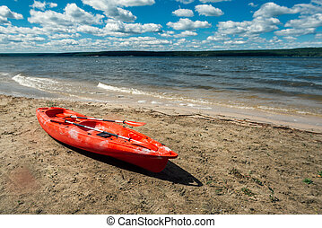 red kayak stands on a sandy shore by the lake
