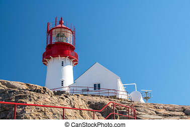 A red lighthouse near a white house on the rocks in the blue ocean