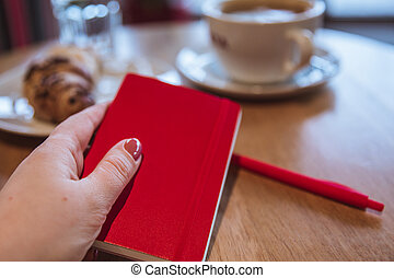 A red note and red pen is on the table in a cafe, a cup of coffee and a croissant on background. Female hand holding a notepad