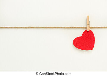A red paper heart hanging from a sisal yarn on white background
