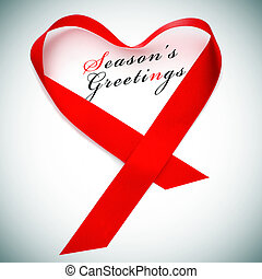 seasons greetings - a red satin ribbon forming a heart and ...