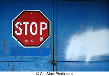 A Red Stop Sign on a Locked Blue Door of an Abandoned Warehouse with Copy Space