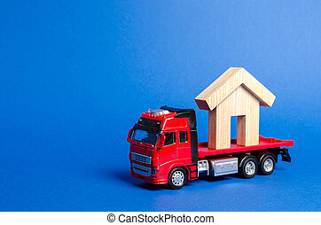 A red truck transports a wooden house. Concept of transportation and cargo shipping, moving company. Construction of new houses and objects. Industry. Logistics and supply. Move entire buildings.