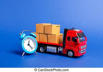 A red truck with cardboard boxes and a blue alarm clock. Express delivery in short time concept. Temporary storage, limited offer and discount. Optimization of delivery logistics. Transport company
