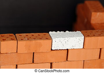 a red wall with one white brick