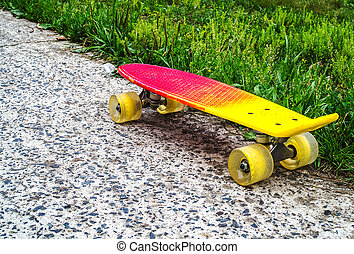 A red-yellow penny board with yellow wheels on the edge of the asphalt and grass transition. Style of freedom and travel in the summer.