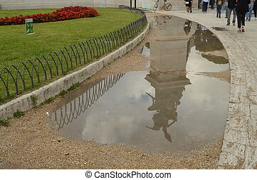 A reflection in a puddle after the rain Statue in the Vittoriano monument of Vittorio Emanuele II in Rome, Italy on October 07, 2018