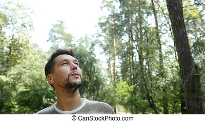A relaxed man looks up and smiles in a pine forest in summer in slow motion