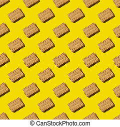 A repeating pattern of yellow crackers on a yellow background. Cookies on a yellow background with hard light can be used as a background