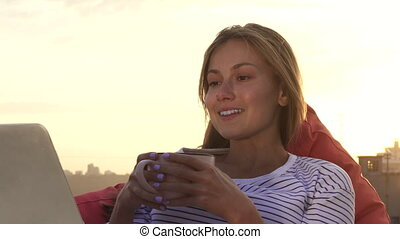 A resting girl drinks warm tea and looks at the laptop sitting on the roof