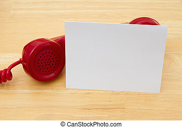 A retro red phone with greeting card