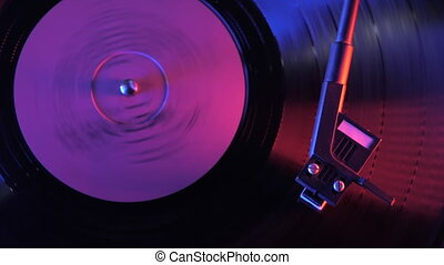 A retro-styled spinning record vinyl player. Vintage video of old gramophone, playing close up. 4k. Time lapse. Beautiful colorful movie. Neon purple led light.