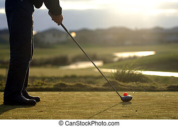 A right handed golfer tees off in the early morning light.