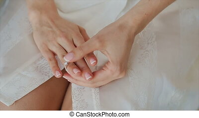 A ring in the hand of a girl who looks at him.