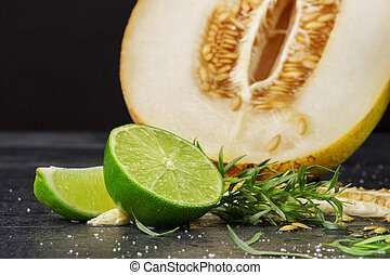 A ripe and raw melon with a lime on a black stone background. A juicy cantaloupe melon cut in half. Sweet and tasty fruits.
