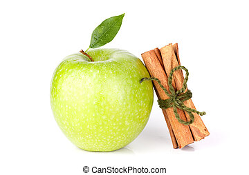 A Ripe Green Apple with water drops and cinnamon sticks