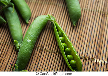 ripe green peas on wooden background