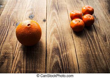 ripe mandarins and orange on a wooden bacground