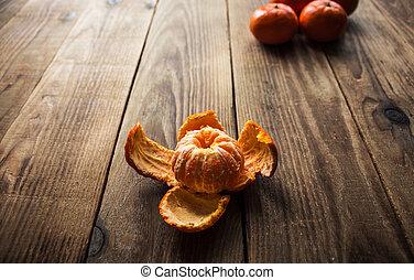 ripe mandarins and peeled mandarin on a wooden bacground