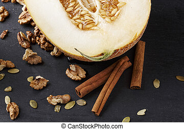 A ripe melon with cinnamon and walnuts on a black background. A juicy cantaloupe melon cut in half. Sweet and tasty fruits.