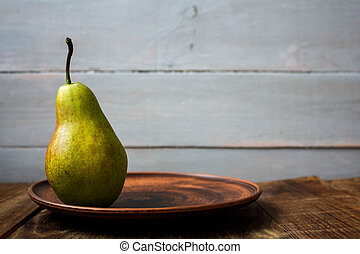 a ripe pear on a plate on wooden background