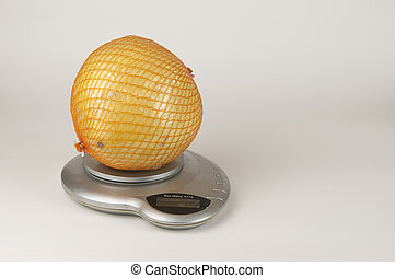 A ripe pomelo is packaged in a grid lies on scales over white background