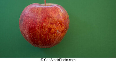 a ripe red apple on green background