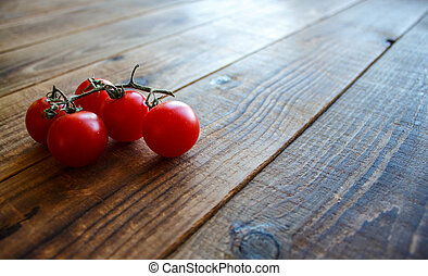ripe tomatoes on a branch on wooden background