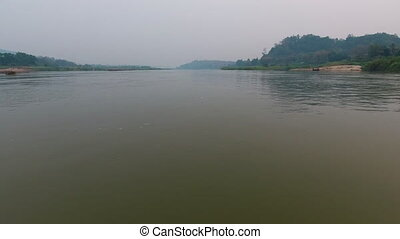 A river bounded by land - Land with green vegetation...
