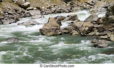 A river falling rapidly between the rocks - A steady, close...