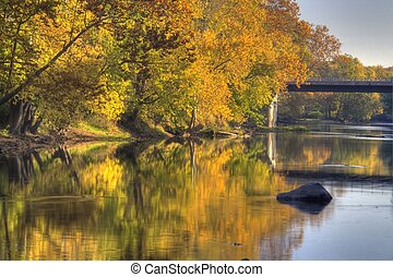 A river flows by brightly colored fall trees with a bridge in the distance.