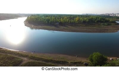 A river in the middle of a forest close to the city. Aerial survey of recreation center