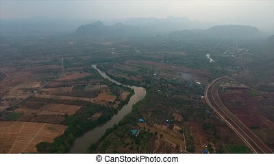 A river passing through farm lands - An aerial shot of a...