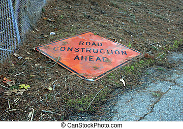 A road construction sign is lying down the street
