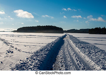A road in snow over a lake in Sweden