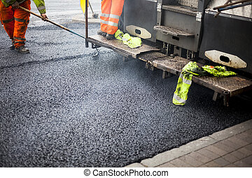 a roadworks on the street new asphalt with worker