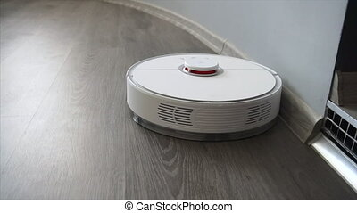 A robotic vacuum cleaner cleans the living room floor. Smart...