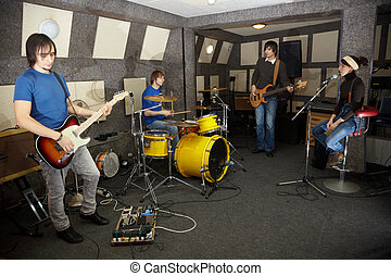 a rock band. vocalist girl, two musicians with electro guitars and one drummer is working in studio