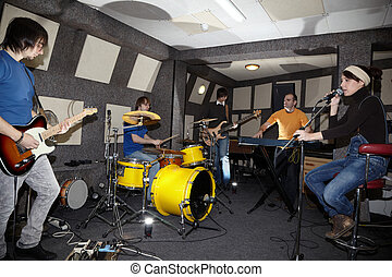 a rock band. vocalist girl, two musicians with electro guitars, keyboarder and one drummer working in studio. flashes in center