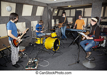 a rock band. vocalist girl, two musicians with electro guitars, keyboarder and one drummer working in studio