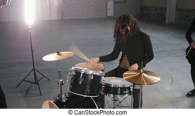 A rock group having a repetition. A man with cool long hair...