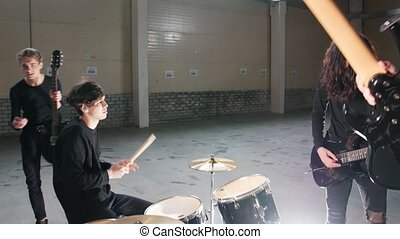 A rock group having a repetition in a hangar. Tuning their...