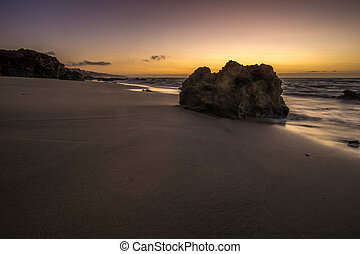 a rock on the beach at sunrise and waves