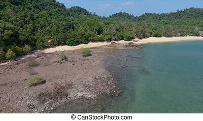 A rocky and sandy beach between a sea and a forest - An high...