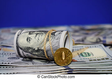 A roll of dollars and a coin of 10 Russian rubles on the background of scattered hundred dollar bills